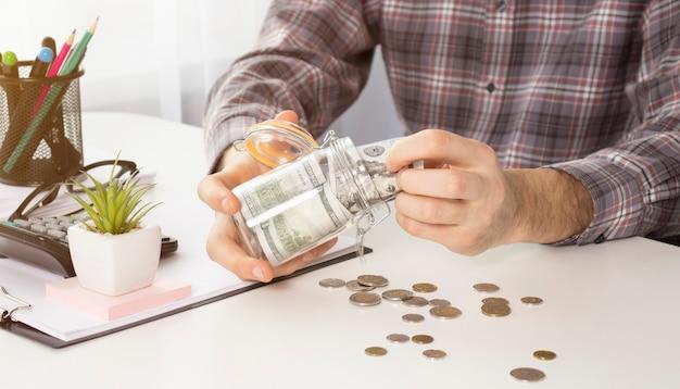 돈 저축으로 유리 항아리에서 동전을 붓는 젊은 여자의 근접 촬영 이미지