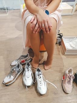 モールに座って新しい靴を試着している若い女性のクローズ アップ画像