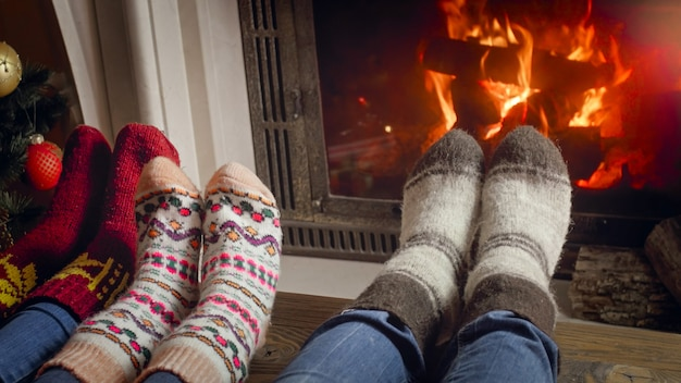 Closeup image of parents with child wearing wool socks relaxing at fireplace