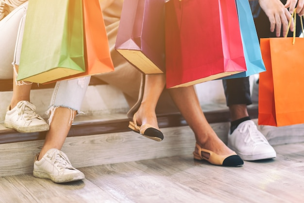 Closeup image of people holding shopping bags while sitting together