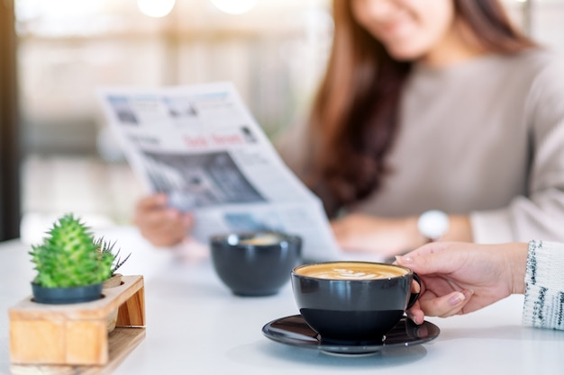Closeup image of people reading newspaper and drinking coffee together in the morning