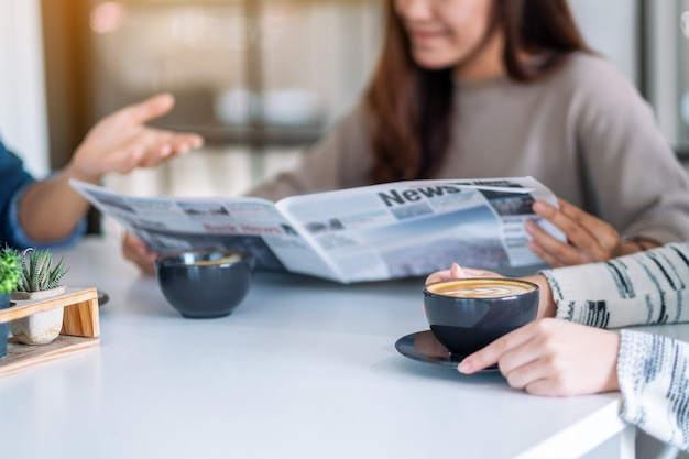Closeup image of people talking, reading newspaper and drinking coffee  together in the morning