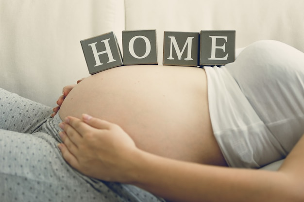 Closeup image of pregnant woman holding word home on belly