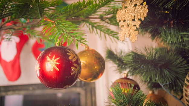 Closeup image of red and golden baubles hanging on christmas tree