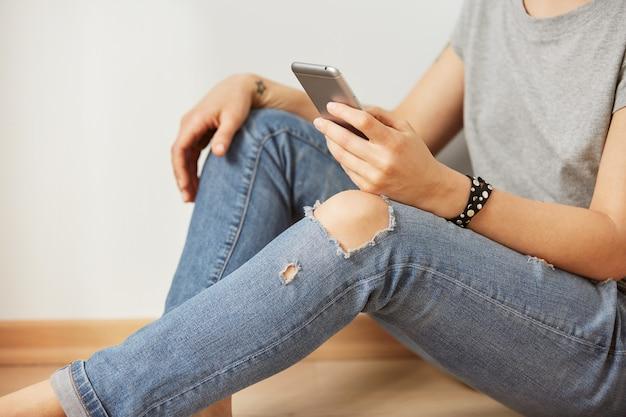 L'immagine del primo piano di un adolescente sta cercando le informazioni nella rete sul telefono cellulare