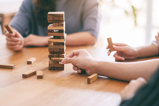 Closeup image of three friends sitting and playing tumble tower wooden block game together
