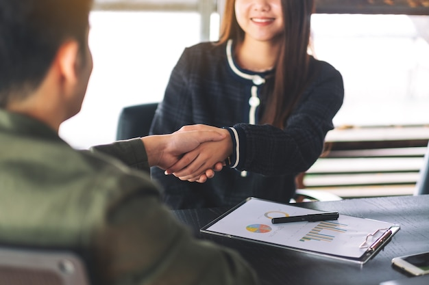 Closeup image of two businesspeople shaking hands in a meeting