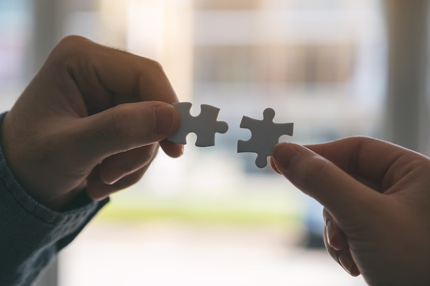 Closeup image of two hands holding and putting a piece of white jigsaw puzzle together