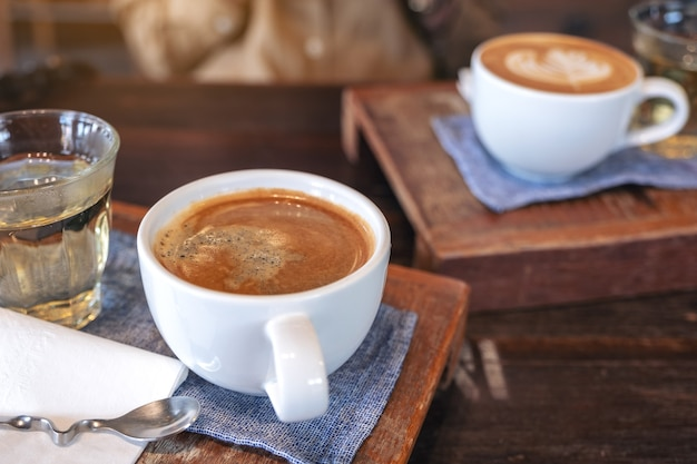 Closeup image of two white cups of hot coffee and a glass of tea on vintage wooden table in cafe