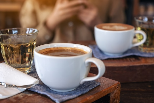 Closeup image of two white cups of hot coffee and a glass of tea on vintage wooden table with a woman in cafe