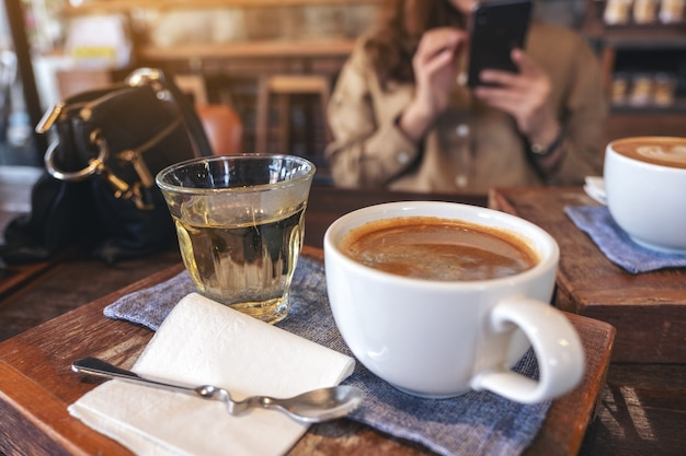 Closeup image of two white cups of hot coffee and a glass of tea on vintage wooden table with a woman using mobile phone in cafe