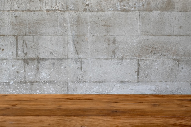 Closeup image of vintage wooden table with concrete wall texture and detail