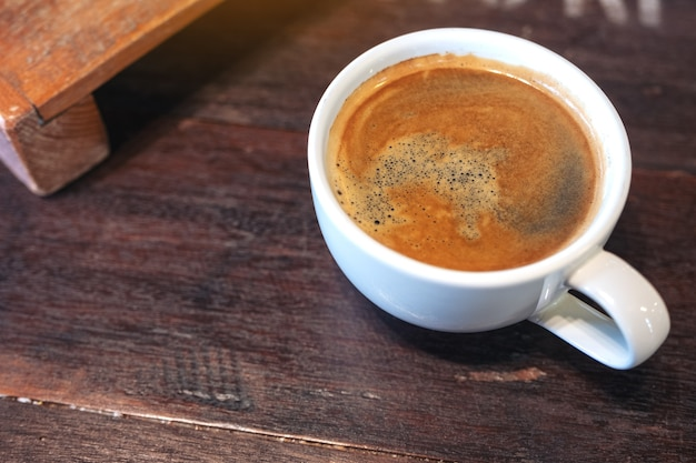 Closeup image of a white cup of hot coffee on vintage wooden table in cafe
