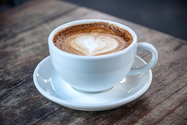 Closeup image of a white cups of hot coffee on vintage wooden table in cafe