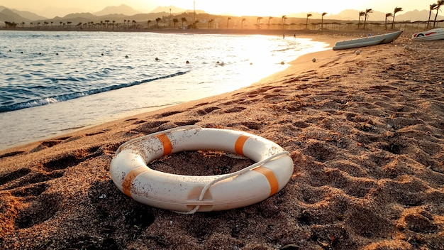 Closeup image of white plastic life saving ring lying on the sandy sea beach against beutiful sunset over the water
