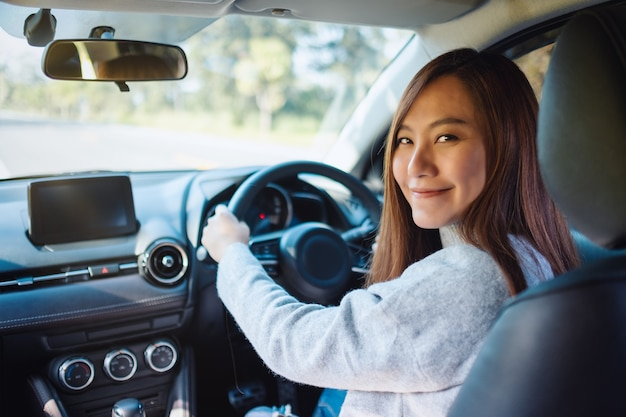 Closeup image of a woman holding steering wheel while driving a car on the road