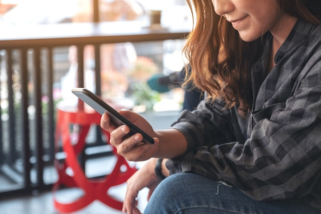 Closeup image of a woman holding , using and looking at smart phone in cafe