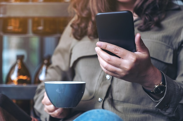 Closeup image of a woman holding , using and looking at smart phone while drinking coffee in cafe