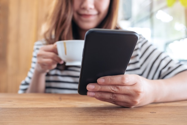 Closeup image of a woman holding , using and looking at smart phone while drinking coffee