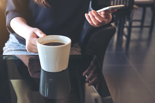 Closeup image of a woman holding and using smartphone while drinking coffee in cafe