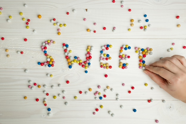 Closeup image of woman making word sweet from colorful candies