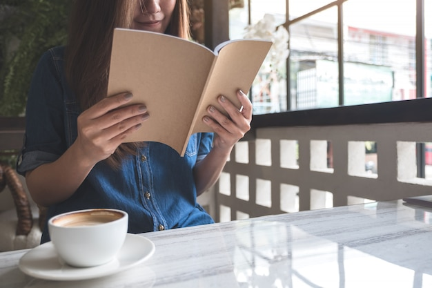 Closeup image of a woman reading a book with coffee cup on table in modern cafe