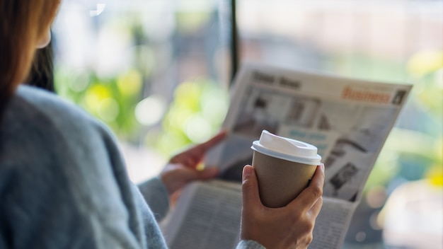 Closeup image of a woman reading newspaper and drinking coffee in the morning
