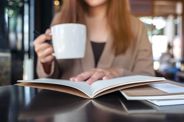 Closeup image of a woman reading and opening a book while drinking coffee in cafe