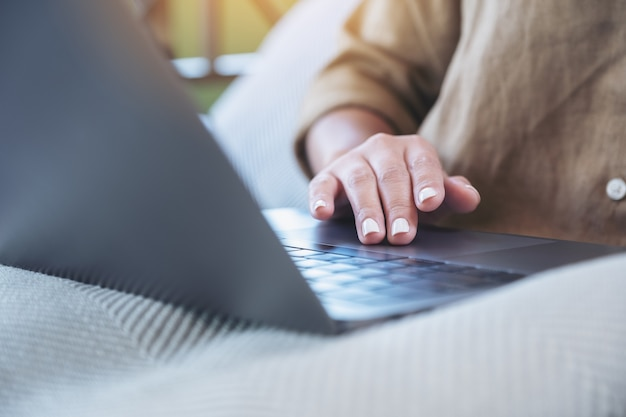 Closeup image of a woman's hand using and touching on laptop touchpad