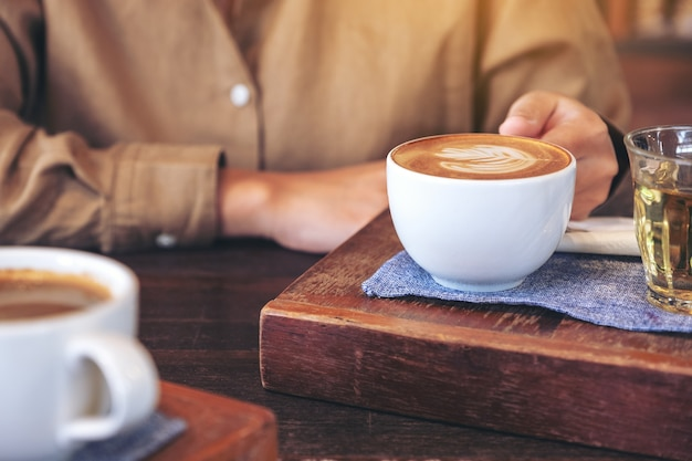 Closeup image of woman's hands holding a cup of hot coffee on wooden table