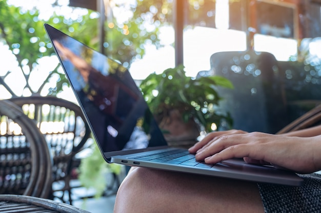Closeup image of woman's hands using and typing on laptop keyboard while sitting in outdoor