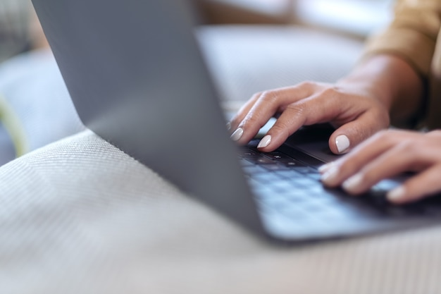 Closeup image of woman's hands using and typing on laptop keyboard