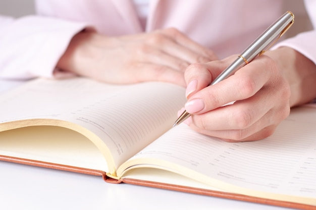 Closeup image of a woman writing down on a white blank notebook on wooden table. pink table, selective focus. business and education concept.