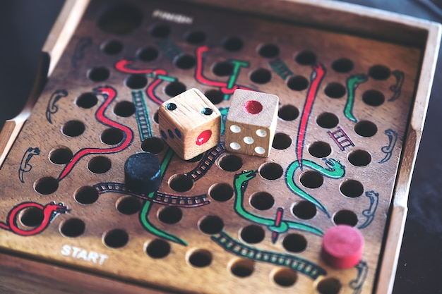 Closeup image of a wooden snakes and ladders game