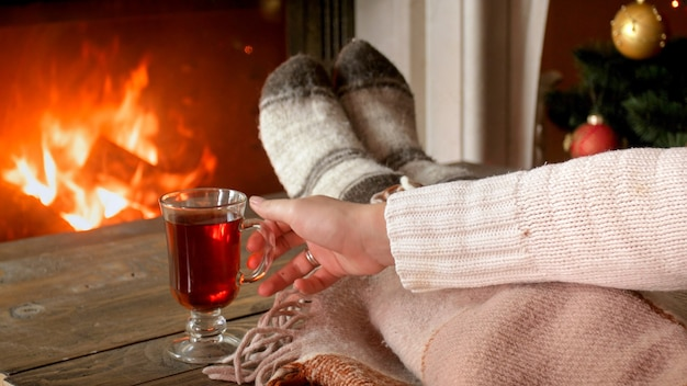 Closeup image of young woman holding cup of tea at burning fireplace