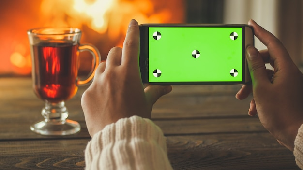 Closeup image of young woman holding mobile phone with green screen next to cup of tea and burning fireplace
