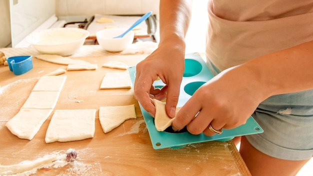 Closeup image of young woman picking up piece of dough and putting it in silicone form for baking in oven