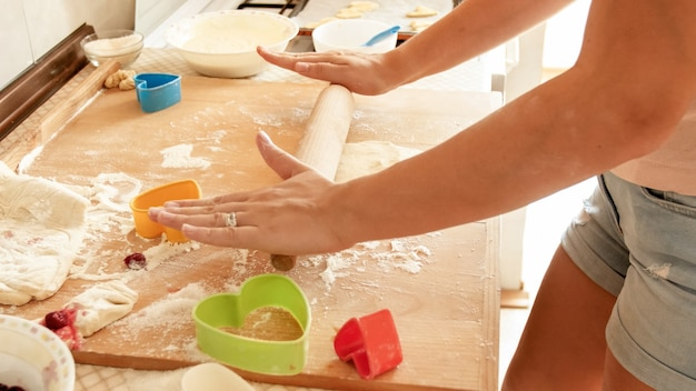 Closeup image of young woman rolling dough with wooden rolling pin