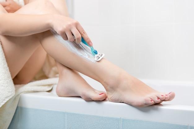 Closeup  image of young woman shaving legs at bathroom