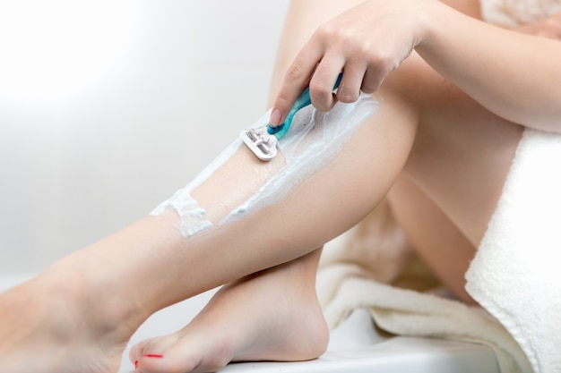 Closeup image of young woman sitting on bath side and shaving legs