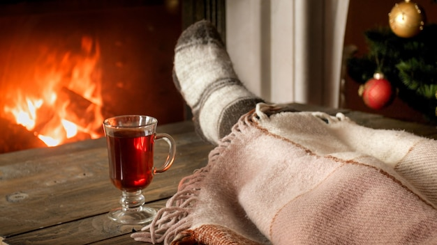 Closeup image of young woman in woolen socks lying under blanket next to burning fireplace with glass of mulled wine