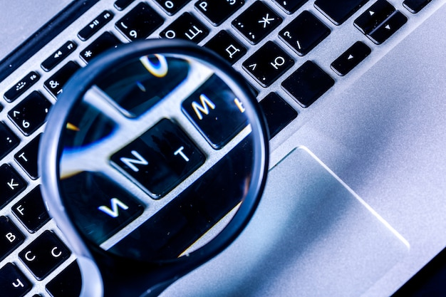 Closeup images of magnifying glass on laptop keyboard