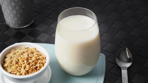 Крупным планом изображения домашнего здорового напитка соевого молока без добавления сахара в стакан на зеленом цвете