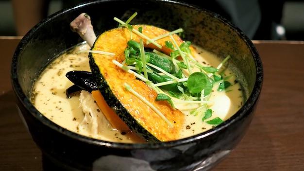 Крупным планом изображения супа карри желтого цвета с курицей, свининой и овощами в миске, которые известны