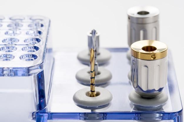 Наборы крупного плана / implant хирургические / мини винт / отвертка / буровые наконечники на белой предпосылке.