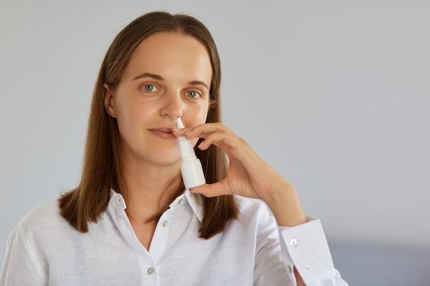Colpo al coperto del primo piano di una donna affascinante che usa spray nasale per il naso che cola, prende il raffreddore, guarda la telecamera, indossa una camicia bianca, posa contro il muro chiaro.