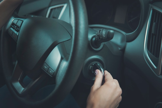 Крупный план внутри транспортного средства женской руки, держащей ключ в зажигании. женщина запускает двигатель автомобиля, поворачивая ключ. руль и женский стартовый автомобиль. девушка приехала к месту назначения и останавливает машину.