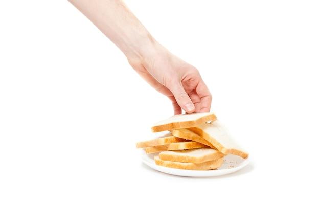 プレートからパンの一部を取って男性の手のクローズ アップの孤立したショット