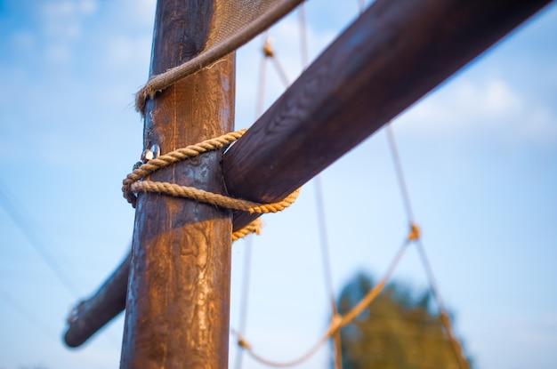 Крупным планом - это деревянный узел, переплетенный с веревкой на мачте корабля на фоне солнечного голубого неба, теплого в летний день. концепт в морской тематике. место для рекламы