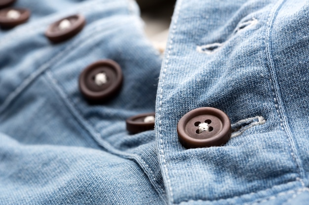 A closeup of jean cardigan with plastic buttons